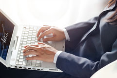 Business woman using laptop computer on sunlight background Royalty Free Stock Photos