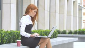 Business woman using laptop with a cup of coffee on the terrace stock video footage