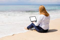 Business woman using laptop with empty white screen on the beach. stock image
