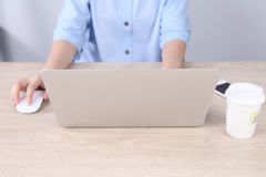 Business woman using laptop with smartphone on wooden desk Royalty Free Stock Photography