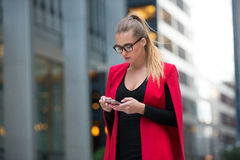 Business woman using mobile application on cell phone and walking from the office building in New York City Royalty Free Stock Image