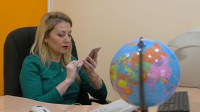Business woman using mobile phone for browsing internet on workspace office. Woman manager typing message by smart phone sitting at desk in travel company stock video