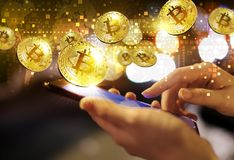 Business woman are using mobile phone with gold bitcoin at city Stock Photo