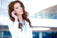 Business woman  using mobile phone. Pretty young business woman  using mobile phone Royalty Free Stock Photos