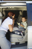 Business Woman Using Mobile Phone With Son In Car Stock Photo