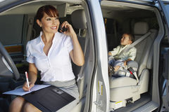 Business Woman Using Mobile Phone With Son In Car Stock Image