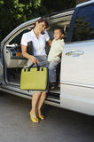 Business Woman Using Mobile Phone With Son In Car Stock Photos
