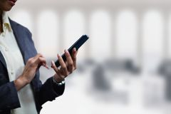 Business woman using a phone against office background Royalty Free Stock Photos