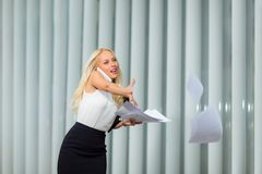 Business woman using a phone and catches the documents Royalty Free Stock Photos