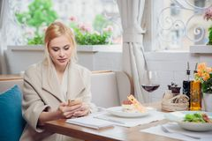Business woman using the smart phone in a restaurant. Beautiful woman waiting for an interlocutor. Anticipation Stock Photo