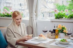 Business woman using the smart phone in a restaurant. Beautiful woman waiting for an interlocutor. Anticipation Royalty Free Stock Photos