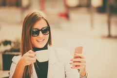Business woman using smart phone. Young  happy business woman using smart phone and drinking coffee in street cafe Royalty Free Stock Photography