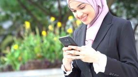 Business woman using smartphone. Muslim business woman using smartphone and smiling stock video footage