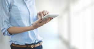 Business woman using a tablet against white blurred background Royalty Free Stock Photography