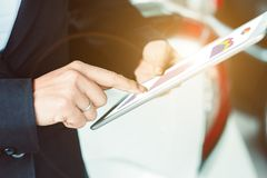 Business woman using tablet checking business information. Closeup business woman using tablet checking business information. with a background as a car Royalty Free Stock Image