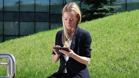 Business woman using a tablet computer. Business woman in suit using a tablet computer outdoor stock footage