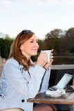 Business woman using tablet on lunch break. Adult business woman using tablet on lunch break in city park Stock Image