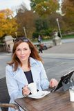 Business woman using tablet on lunch break. Royalty Free Stock Photography