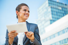 Business woman using tablet pc in front of office Royalty Free Stock Image
