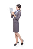 Business woman using tablet PC in full length Royalty Free Stock Photos