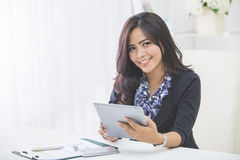 Business woman using tablet pc. Smiling business woman using tablet pc while sitting in the office Stock Images