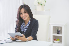 Business woman using tablet pc. Smiling business woman using tablet pc while sitting in the office Stock Photography