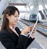 Business woman using touch pad in the train statio. Young business woman using touch pad in the train station Stock Photography