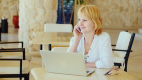 Business woman on vacation. Sits by the laptop, talking on the phone. In light summer clothes.  stock video footage