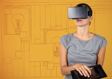 Business woman in virtual reality headset with tablet against orange hand drawn wall with pictures Royalty Free Stock Image