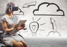 Business woman in VR with tablet against lightbulb doodles on wall. Digital composite of Business woman in VR with tablet against lightbulb doodles on wall Stock Photo