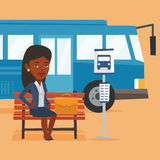 Business woman waiting at the bus stop. African-american business woman with briefcase waiting at the bus stop. Businesswoman sitting at the bus stop Stock Photo