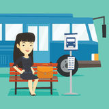 Business woman waiting at the bus stop. Asian business woman with briefcase waiting at the bus stop. Young business woman sitting at the bus stop. Business Stock Photo