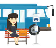 Business woman waiting at the bus stop. Asian business woman waiting at the bus stop. Young business woman sitting at the bus stop. Business woman sitting on a Stock Images