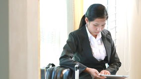 Business woman waiting for travel and using tablet computer stock footage