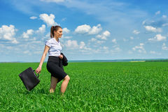 Business woman walk on green grass field outdoor. Beautiful young girl dressed in suit, spring landscape, bright sunny day royalty free stock photo