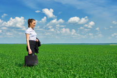 Business woman walk on green grass field outdoor. Beautiful young girl dressed in suit, spring landscape, bright sunny day Royalty Free Stock Photography