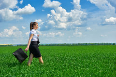 Business woman walk on green grass field outdoor. Beautiful young girl dressed in suit, spring landscape, bright sunny day Stock Image