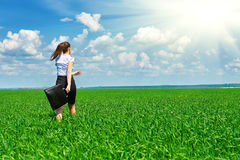Business woman walk on green grass field outdoor and relax under sun. Beautiful young girl dressed in suit resting, spring landsca Stock Photography