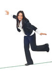 Business woman walk on tightrope. Business woman walking on a tight rope and trying to keep her balance isolated on white background Stock Photo