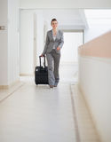 Business woman walking with bag on wheels Stock Photos