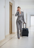 Business woman walking with bag on wheels Stock Photography