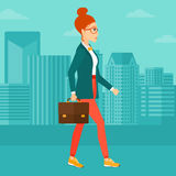Business woman walking with briefcase. A woman walking with a briefcase on the background of modern city vector flat design illustration. Square layout Royalty Free Stock Photography