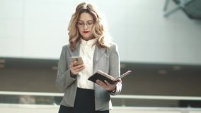 Young woman in business suit typing message on mobile phone. portrait of a business woman in an office building. Business woman walking on business center with stock video
