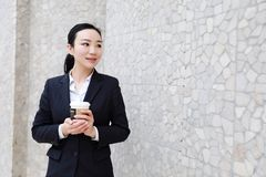 Business woman walking drinking coffee. Lawyer professional or similar walking outdoors happy holding disposable paper cup. Multiracial Asian / Caucasian royalty free stock images