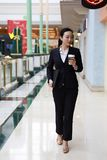 Business woman walking drinking coffee and Notebook computer in shopping mall. Business woman walking drinking coffee. Lawyer professional or similar walking Stock Images
