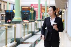 Business woman walking drinking coffee in shopping mall. Business woman walking drinking coffee. Lawyer professional or similar walking outdoors happy holding stock photography