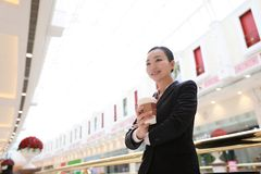 Business woman walking drinking coffee in shopping mall. Business woman walking drinking coffee. Lawyer professional or similar walking outdoors happy holding royalty free stock photography