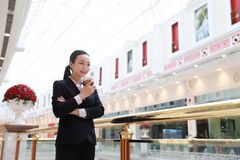 Business woman walking drinking coffee in shopping mall. Business woman walking drinking coffee. Lawyer professional or similar walking outdoors happy holding royalty free stock images