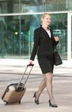 Business woman walking int he city with travel bag and luggage. Portrait of a business woman walking int he city with travel bag and luggage Royalty Free Stock Photography