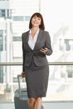 Business woman walking with mobile phone and luggage Stock Photos